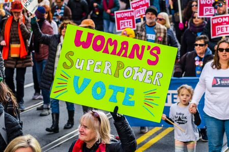 Jan 18, 2020 San Francisco  CA  USA - Participant to the Womens March event holds Womans Superpower Vote sign while marching on Market street in downtown San Francisco