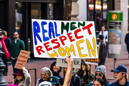 Jan 18, 2020 San Francisco  CA  USA - Participant to the Womens March event holds Real Men Respect Women sign while marching on Market street in downtown San Francisco
