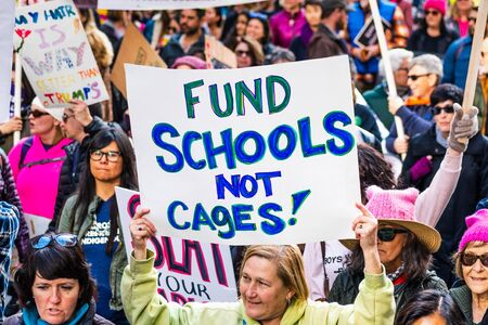 Jan 18, 2020 San Francisco  CA  USA - Participant to the Womens March event holds Fund Schools Not Cages sign while marching on Market street in downtown San Francisco