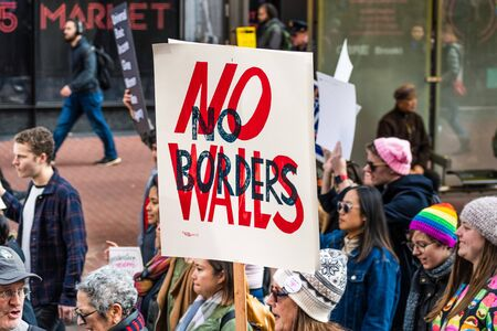 Jan 18, 2020 San Francisco  CA  USA - Participant to the Womens March event holds No Borders No Walls sign while marching on Market street in downtown San Francisco