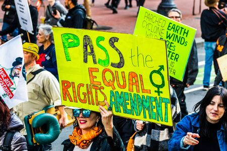 Jan 18, 2020 San Francisco  CA  USA - Participant to the Womens March event holds Pass the Equal Rights Movement sign while marching on Market street in downtown San Francisco
