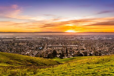 Sunset view of residential and industrial areas in East San Francisco Bay Area; green hills visible in the foreground; Hayward, California 版權商用圖片 - 138270527