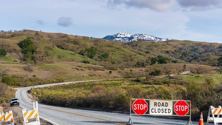 Road Closed sign posted on Mt Hamilton road due to snow, South San Francisco Bay Area, California; snow visible on the summit in the background