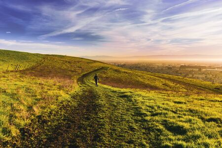 Sunset view of hiker walking on a trail on the verdant hills of East San Francisco Bay Area; California