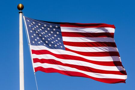 Beautifully waving star and striped American flag on a blue sky background; Close Up for Memorial Day or 4th of July