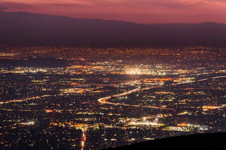 Panoramic night view of urban sprawl in San Jose, Silicon Valley, California; Visible light trail left by cars driving on one of the freeways; long exposure