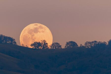 Full moon rising from behind a hill in the Diablo Mountain Range, in South San Francisco Bay Area, San Jose, California; visible distortion due to heat and pollution