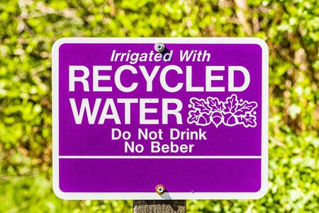Close up of Irrigated with Recycled Water; Do Not Drink sign posted in a public park in Santa Clara, South San Francisco Bay Area, California