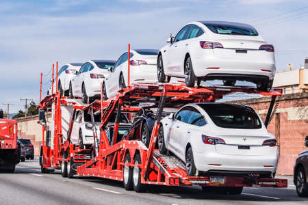 Jan 18, 2020 Palo Alto / CA / USA - Car transporter carries Tesla Model 3 new vehicles on a freeway in San Francisco bay area, back view of the trailer;