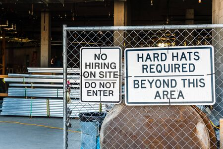 Signs at the entrance to a construction site stating that there is no hiring on site and hard hats are required beyond this area and cautioning people to not enter