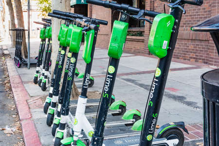Oct 20, 2019 San Jose / CA / USA - Lime and Lyft electric scooters parked on a sidewalk in the downtown area; both companies have discontinued operations in the city due to the Covid-19 outbreak