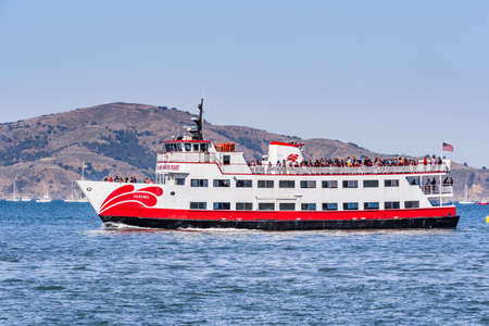 Oct 12, 2019 San Francisco / CA / USA - Red and White Fleet sightseeing ship cruising in the San Francisco Bay; Angel island visible in the background