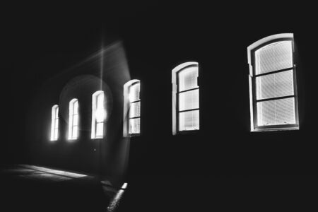 Bright light shinning through a row of windows in the middle of the night; black and white Banco de Imagens