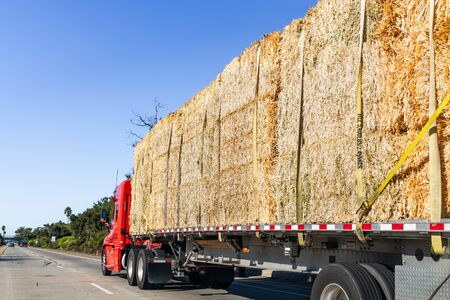 Truck transporting bales of hay on a freeway in Ventura County, South California