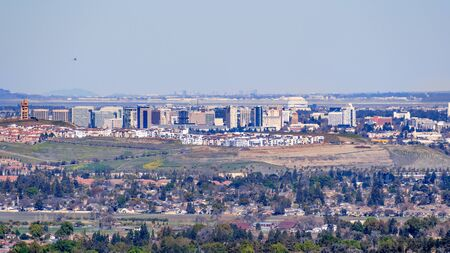 Aerial view of the San Jose downtown skyline on a clear day; residential neighborhoods visible in the foreground; south San Francisco bay, California