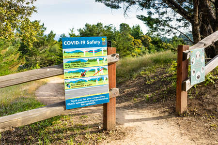 May 10, 2019 Redwood City / CA / USA - COVID-19 Safety signage, explaining the applicable social distancing rules, displayed at the entrance of a hiking trail in Santa Cruz mountains Editorial