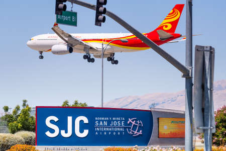 July 23, 2020 San Jose / CA / USA -  San Jose International airport (SJC) sign displayed at the entrance to the airport; Hainan Airlines Dreamliner in the process of landing visible in the background