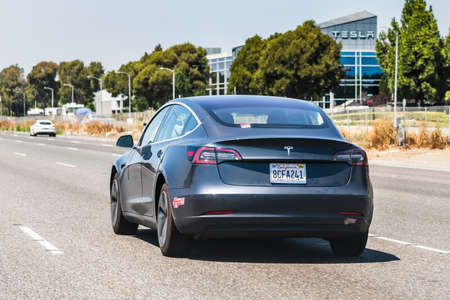 July 26, 2020 Fremont/ CA / USA - Tesla Model 3 travelling on the freeway in Silicon Valley, close to the factory; Tesla office building visible in the background; East San Francisco bay area