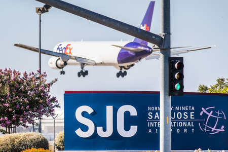 August 7, 2020 San Jose / CA / USA - San Jose International airport (SJC) sign displayed at the entrance to the airport; Fedex aircraft in the process of landing visible in the background 新闻类图片