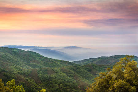 Sunset views in Santa Cruz mountains; Smoke from the nearby burning wildfires, visible in the air and covering the mountain ridges and valleys; South San Francisco Bay Area, California