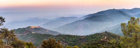 Panoramic sunset views in Santa Cruz mountains; Smoke from the nearby burning wildfires, visible in the air and covering the mountain ridges and valleys; South San Francisco Bay Area, California