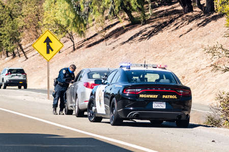 Oct 14, 2020 Fremont / CA / USA - Highway Patrol officer writing a traffic ticket to a driver pulled over on the right side of the road 新闻类图片