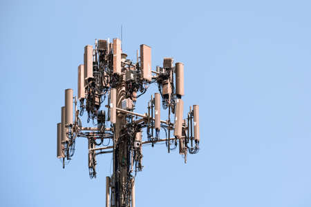 Close up of telecommunications cell phone tower with wireless communication antennas; blue sky background and copy space on the right 免版税图像