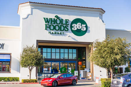 Oct 31, 2020 Concord / CA / USA - Whole Foods store located in East San Francisco Bay Area; Red Tesla Model 3 driving by 新闻类图片