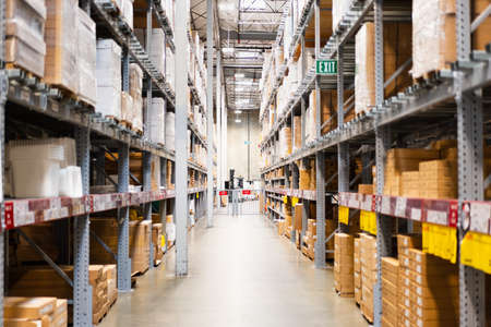 Warehouse interior view, with boxes stacked up high on both sides of an aisle