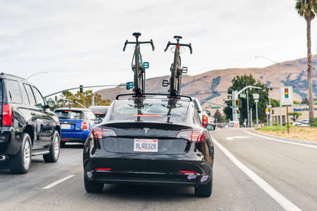 Oct 10, 2020 Fremont / CA / USA - Rear view of Tesla Model 3 with two bicycles mounted on the roof, stopped at a traffic sign in Silicon Valley; East San Francisco bay area