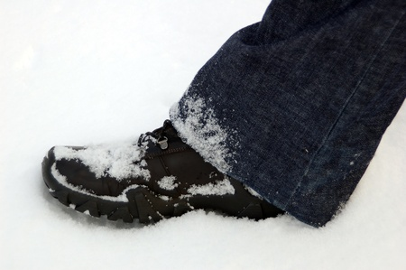 Black boot and footprint in fresh white snow photo
