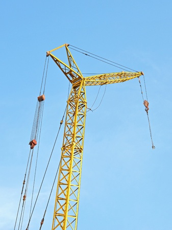 Mobile yellow construction tower crane against blue sky  photo