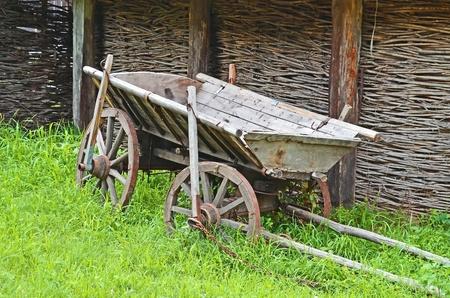 Ancient wooden cart standing on a green grass Stock Photo - 10331435