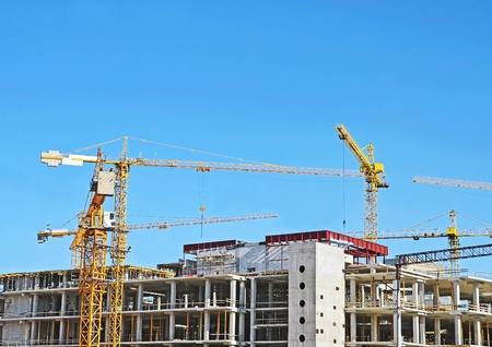 Crane and building construction site against blue sky Stock Photo - 10680782