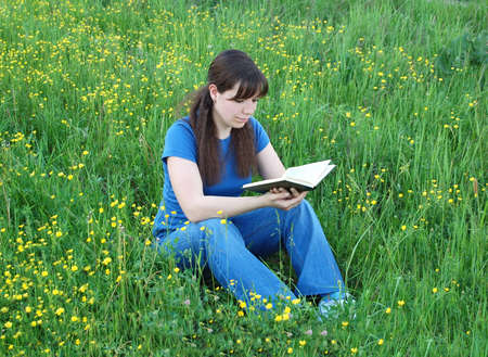 Young woman reading a book at the meadow photo