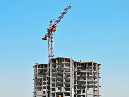 Crane and building construction site against blue sky Stock Photo - 12778883