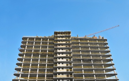 Building crane and building under construction against blue sky photo