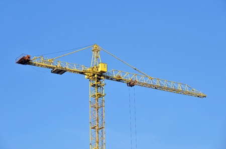 Yellow construction tower crane against blue sky Stock Photo - 12929630