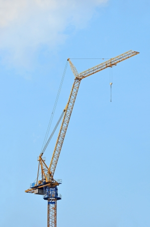Yellow construction tower crane against blue sky Stock Photo - 13625924