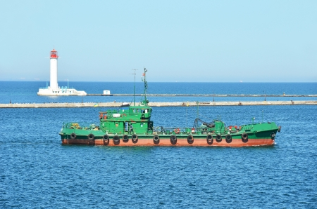 Old industrial pilot ship and lighthouse in Black sea photo