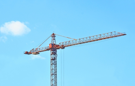 Red construction tower crane against blue sky photo