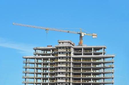 Bouwen kraan en gebouw in aanbouw tegen de blauwe hemel