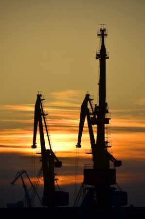 Port cargo crane over sunset sky background photo