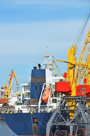 Pipe stack and ship under crane bridge photo