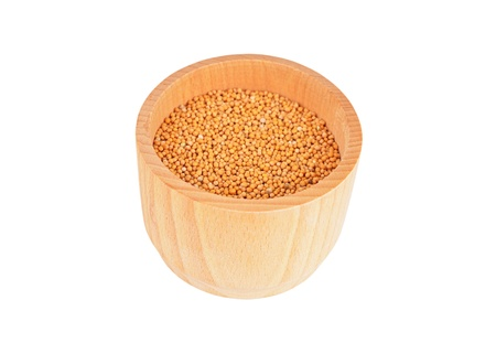 Mustard seeds in wooden bowl, isolated on white background  photo