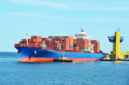 maritime: Tugboat assisting container cargo ship to harbor quayside