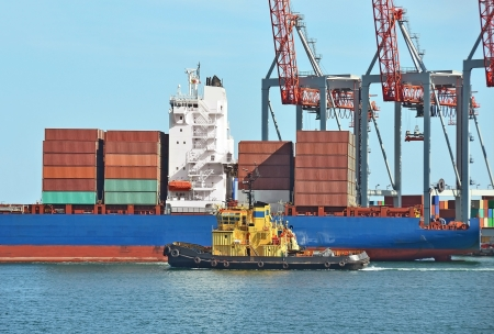 maritime: Container stack, ship and tugboat under crane bridge Stock Photo