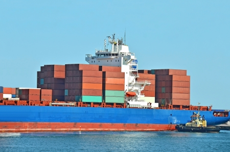 Tugboat assisting container cargo ship to harbor quayside Stock Photo - 16272575