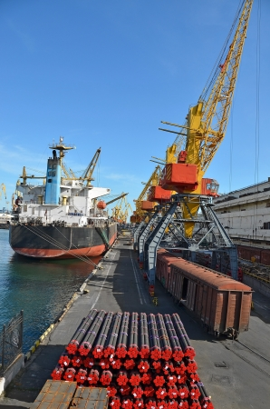 Pipe stack, ship ans train under crane bridge Stock Photo - 17003138