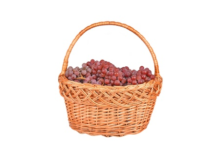 Red grape in a wattled basket, isolated on a white background photo